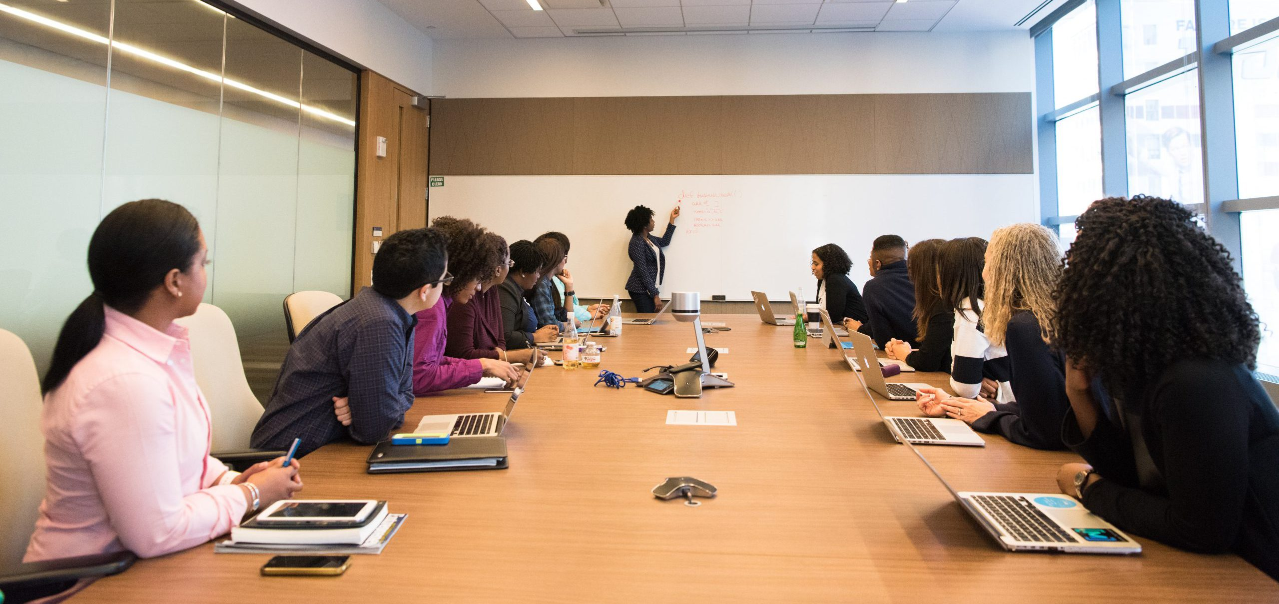 business professionals having meeting inside conference room looking at whiteboard