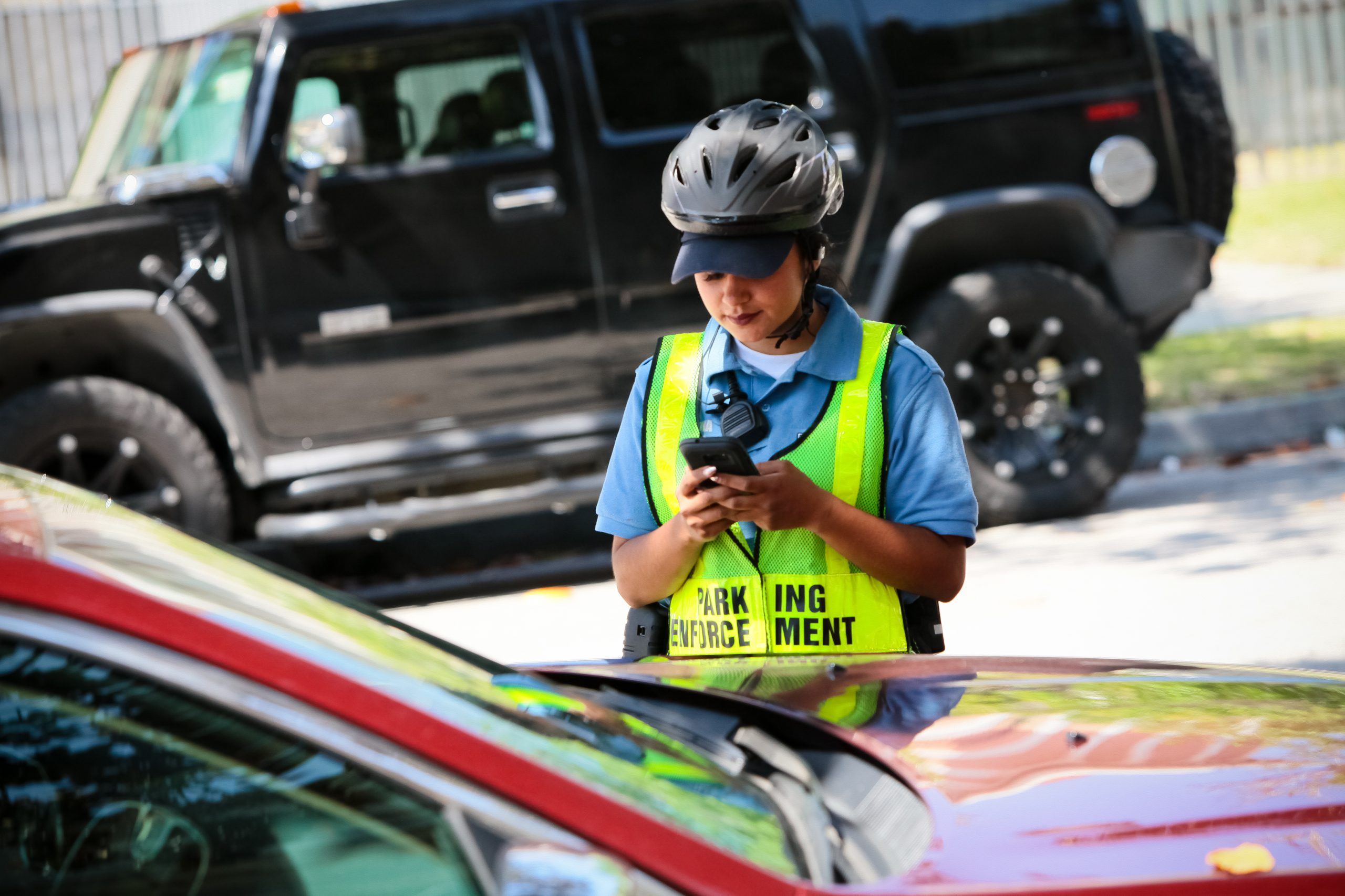 Parking enforcement services - officer looking at phone in front of car