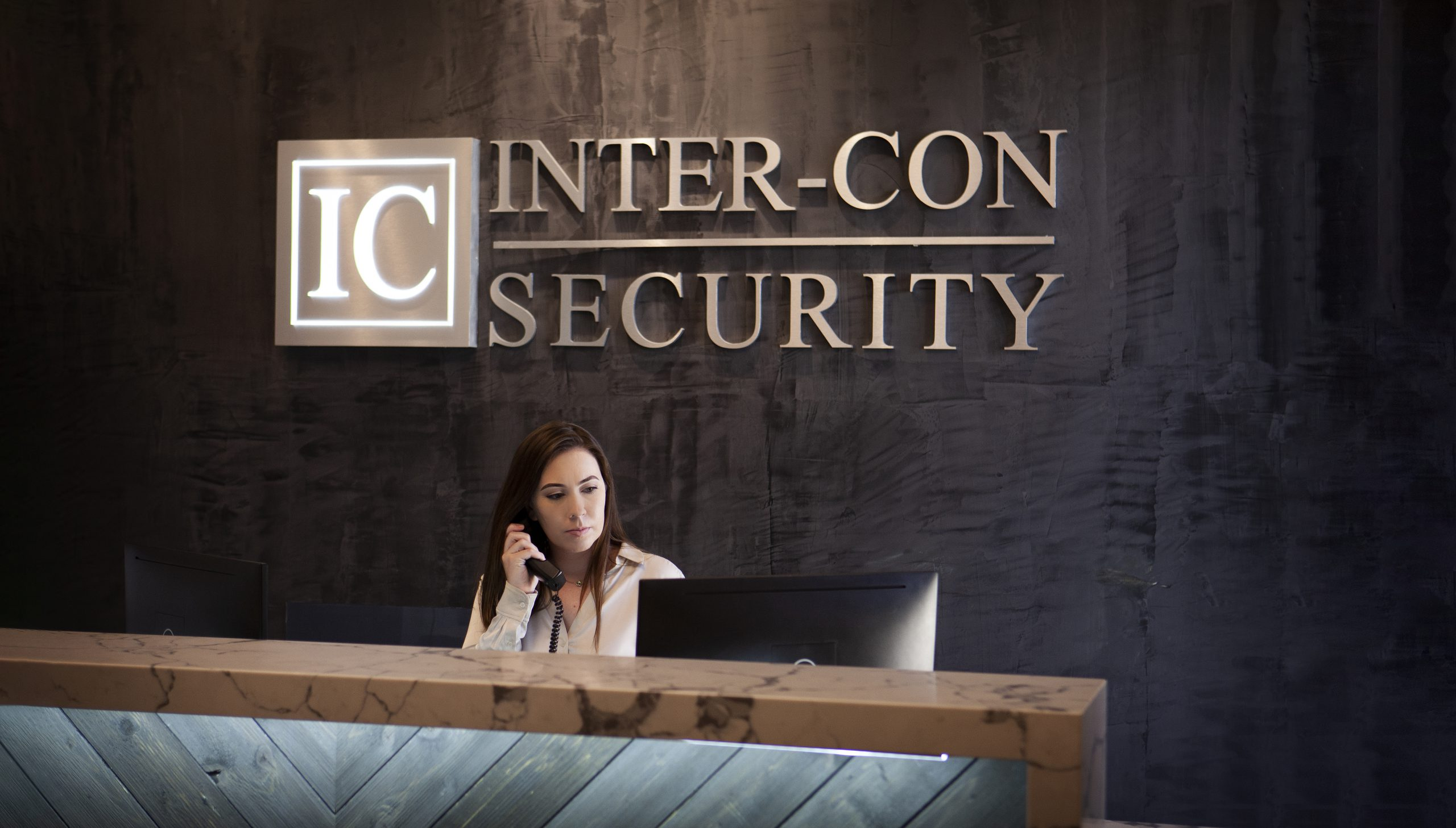 Concierge receptionist with phone sitting behind desk at inter-con security building
