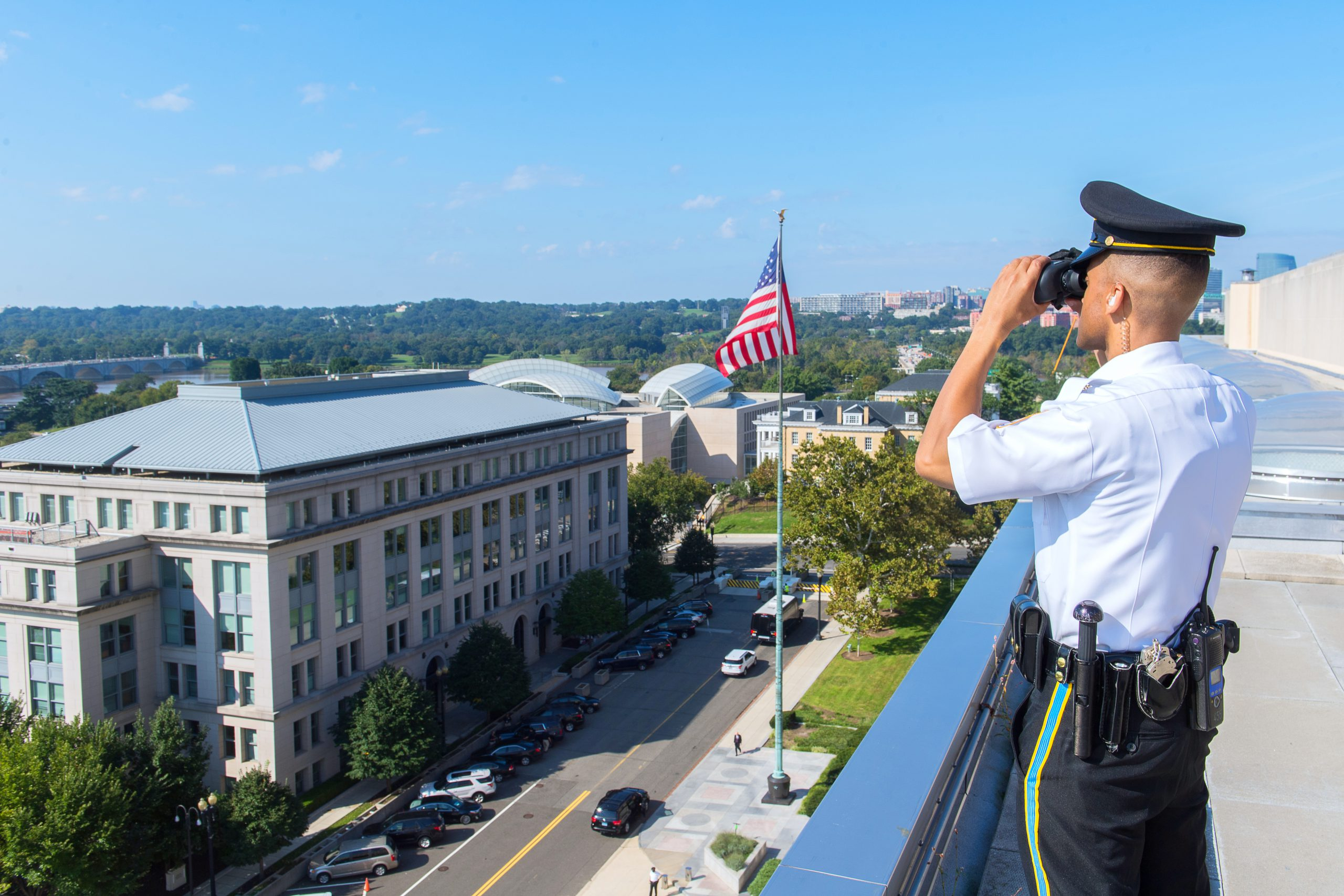 Security Officer looking through binoculars on top of building